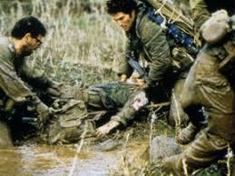 A group of soldiers try to pick up a wounded comrade from the mud
