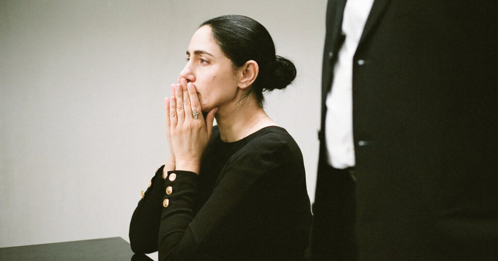 A woman covers her mouth with her hands. A man in a suit stands next to her