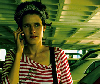 A woman in a red and white striped shirt talks on a cell phone.