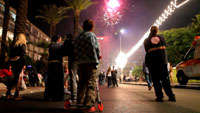 A group of people stand in the street watching fireworks at night