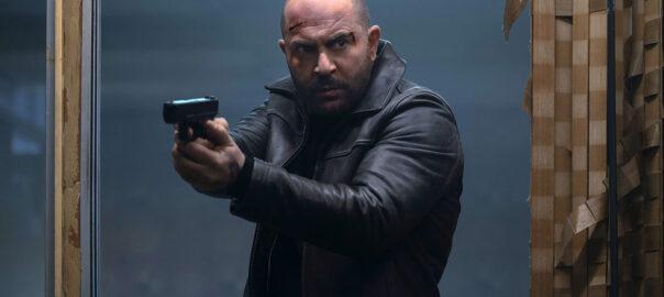 A man in a dark jacket holds a gun.