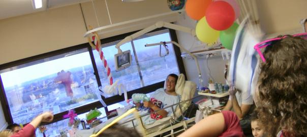 A young man lies in a hospital bed surrounded by balloons